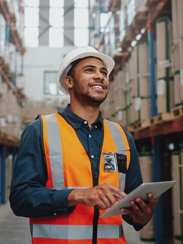 man in warehouse holding tablet